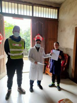 罗焘(左一)和村医陈立德上门指导需按规定进行隔离的群众签订《自我隔离承诺书》
