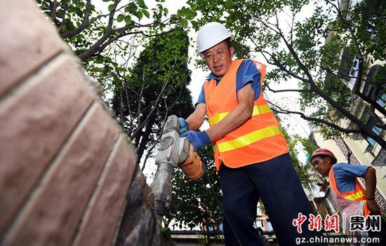 """图为7月6日,在贵阳市南明区西湖路街道""""三感社区""""试点项目建设现场,施工工人正在进行绿化带提升作业。"""