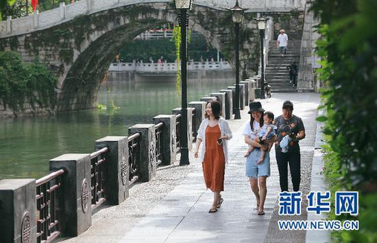 7月10日,人们在南明河畔休闲散步。新华网 卢志佳 摄