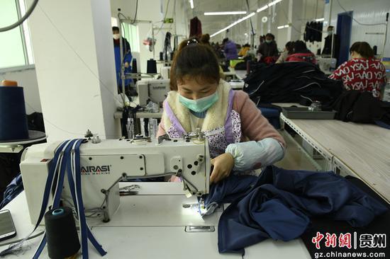 织金县惠民街道易地扶贫搬迁点扶贫车间的工人在缝制裤腿。秦海艳 摄