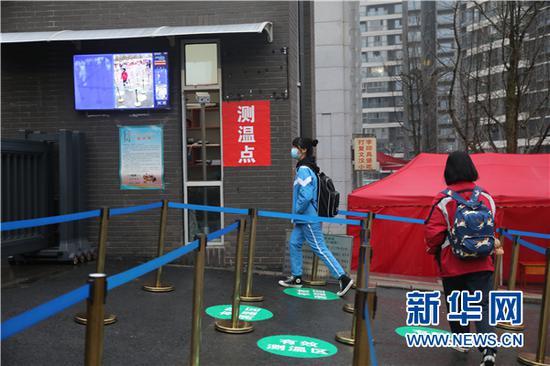 3月16日,学生在进入学校时通过体温监测点。新华网 卢志佳 摄