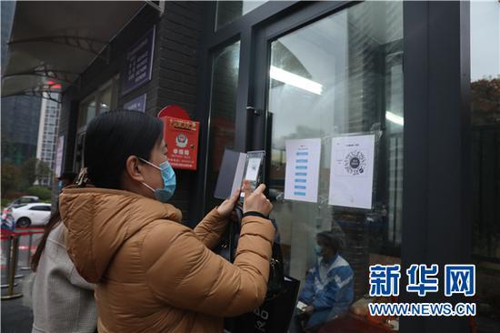 """3月16日,贵阳市第二实验中学的教职员工在进入学校前扫""""健康码""""。新华网 卢志佳 摄"""