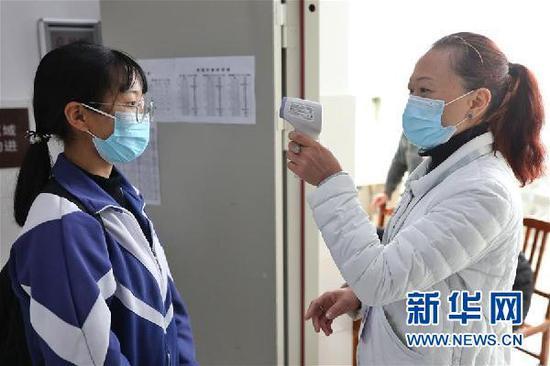 3月16日,贵阳市第六中学高三住校学生在进入宿舍前接受体温检测。新华社记者 欧东衢 摄