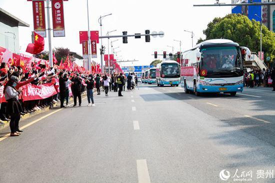 在贵阳龙洞堡机场,群众自发在道路两旁迎接返回的医疗队员。李宇 摄