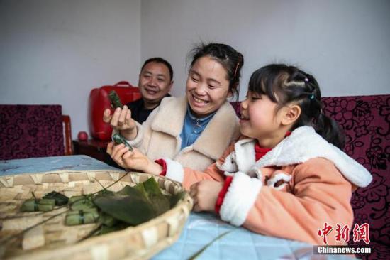 """图为2月4日,贵州黔西化屋村村民赵玉学(左一)一家在制作黔西名小吃""""黄粑""""。 中新社记者 瞿宏伦 摄"""