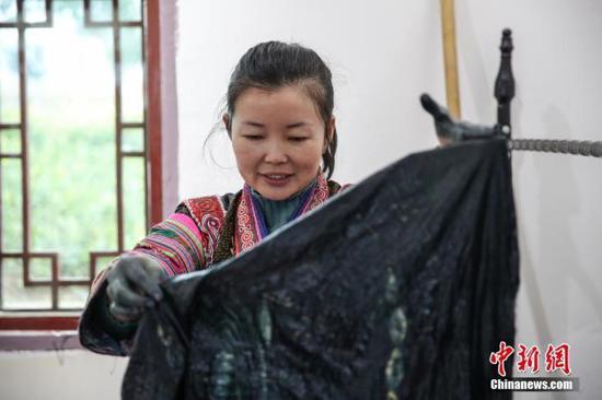图为2月4日,贵州黔西化屋村扶贫车间擅长蜡染工艺的彭艺在染制产品。 中新社记者 瞿宏伦 摄