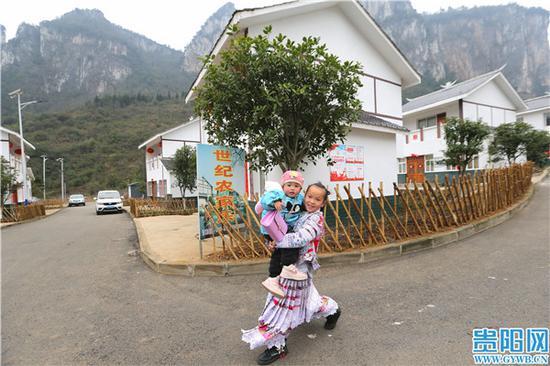 化屋村易地扶貧搬遷點上,一名當地少數民族村民喜笑顏開。