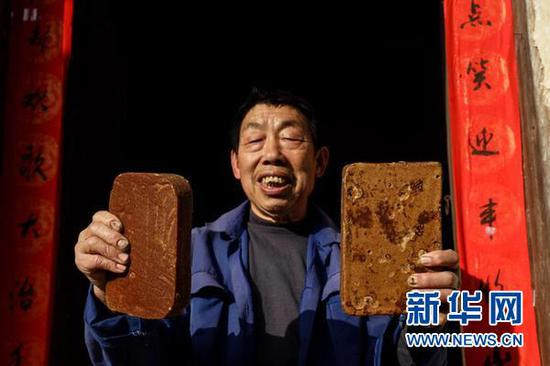 72岁的宋光平在展示自己亲手做的红糖。当年救助过红军的红糖,现在成了村民致富发展的支柱产业。(新华社记者欧东衢2021年4月21日摄)