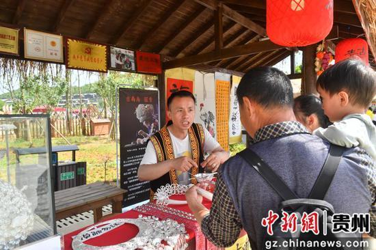党员诚信经营户为游客介绍产品。