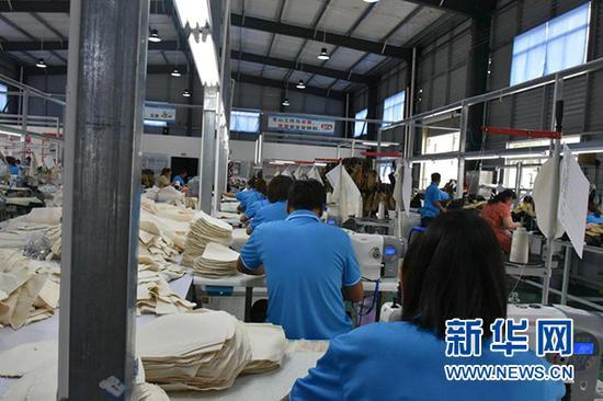工人在鄢家山社区扶贫车间里生产皮包(6月8日摄)。新华社记者 施钱贵 摄