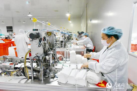 1月29日晚,漳浦县健德医疗器械有限公司厂房内工人加紧生产医用口罩。余杉芳摄