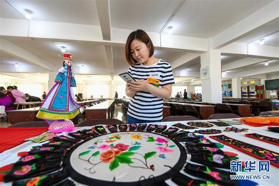 在内蒙古兴安盟科尔沁右翼中旗刺绣扶贫车间内的工艺品展示区,前来参观的游客在拍摄展品(2019年4月18日摄)。新华社记者 彭源 摄