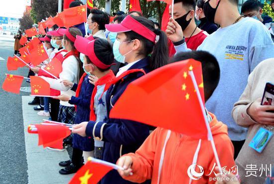 热心市民手持国旗等待英雄归来。王秀芳 摄