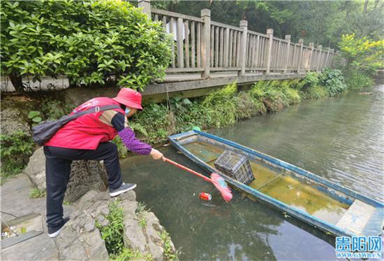 黔灵山公园内,保洁阿姨清洁湖水中的垃圾