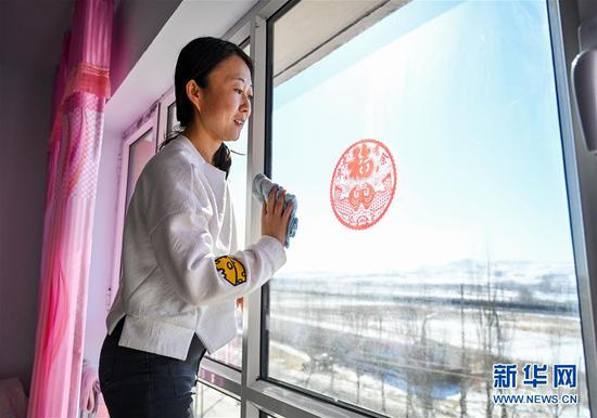 在内蒙古乌兰察布市卓资县易地搬迁房福安小区,今年在读大四的王清在擦窗户(2020年3月27日摄)。新华社记者 连振 摄