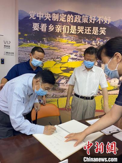 图为贵州部分省级离退休干部在展馆留言簿上留言。 罗兴 摄