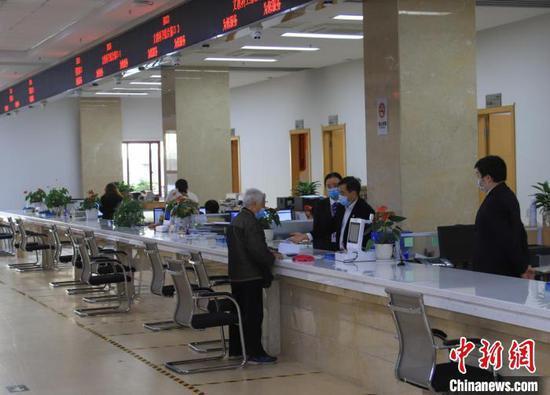 图为贵州省政务服务大厅窗口工作人员为老年人办事。贵州省政务服务中心供图
