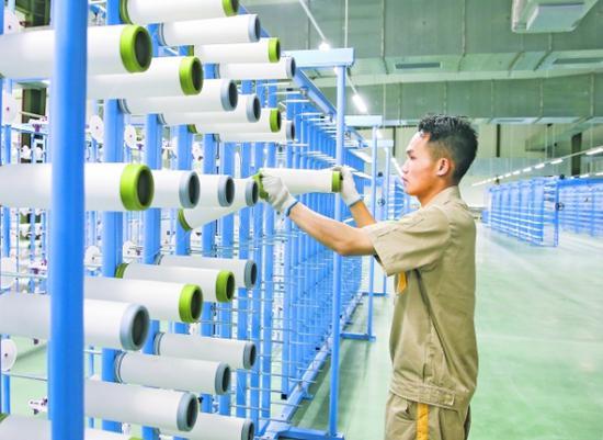 工人在恒力(貴陽)產業園分條整經車間收筒角絲。