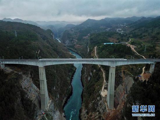 一列从贵阳北到重庆西的动车行驶在贵州省遵义市境内的乌江大桥上(1月25日无人机拍摄)。新华社记者 刘续 摄