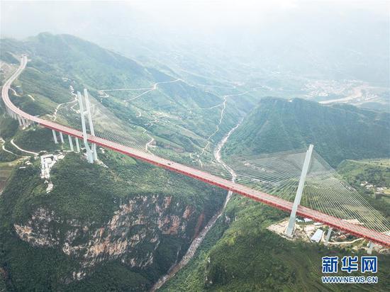 """位于贵州、云南交界处杭瑞高速上的北盘江大桥(8月10日无人机拍摄)。其桥面至江面565.4米的垂直高度,被吉尼斯官方认证为""""世界最高桥""""。(新华社记者 陶亮 摄)"""