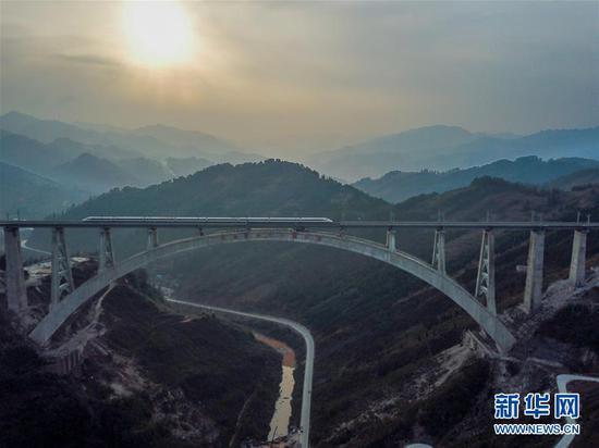 """一列动车组测试列车驶过夜郎河特大桥(1月11日无人机拍摄)。该桥位于贵州省桐梓县境内,主桥设计采用""""提篮式""""钢管骨架拱桥,最大跨度370米。(新华社记者 欧东衢 摄)"""