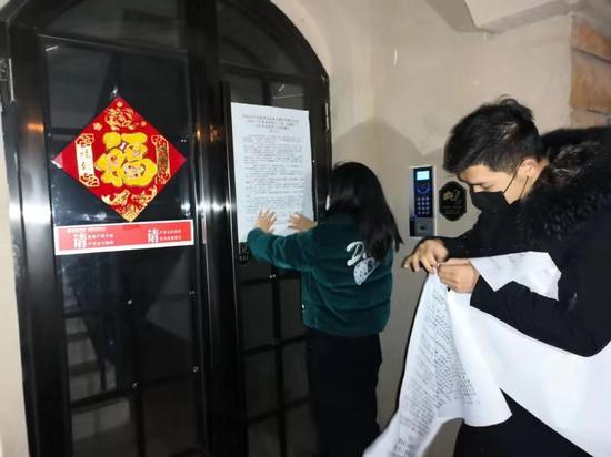 工作人员冒着严寒深入居民楼栋张贴疫情防控公告