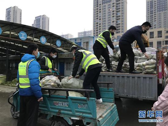 蘿卜運抵鄭州后,志愿者幫助卸車(2月5日攝)。新華社發