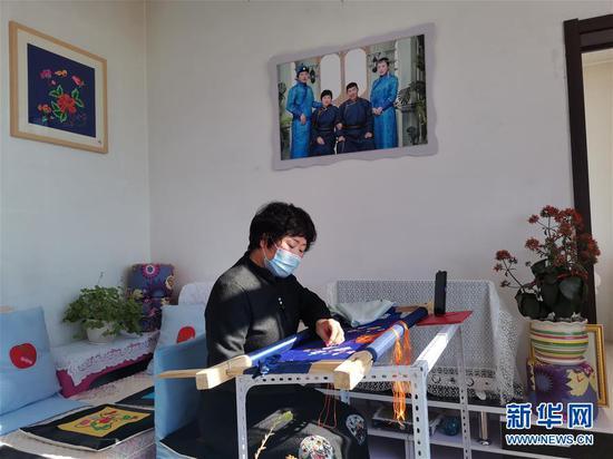 内蒙古兴安盟科尔沁右翼中旗绣娘王金莲在家通过手机视频教授蒙古族刺绣(2020年2月27日摄)。新华社发(白俊华摄)