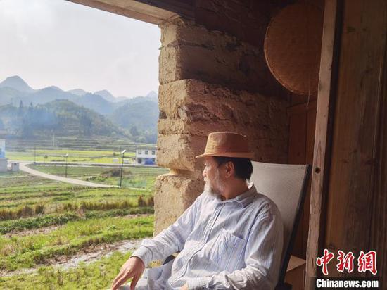 """艺术家嵩田坐在""""认养""""的老屋看外面的风景。 周燕玲 摄"""