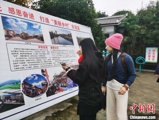 11月22日,两岸媒体文化交流参访团来到花茂村。图为参访团成员观看花茂村宣传板。 张舵 摄