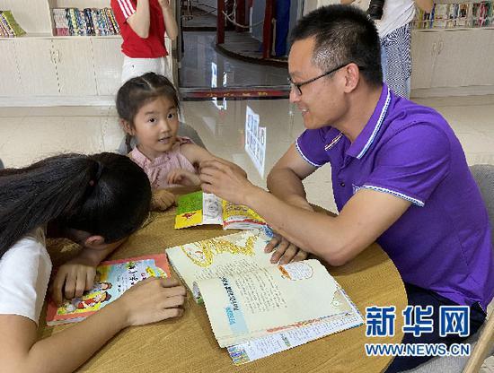 安慧婷(中)和安荣正在阅读。新华网 王雪松 摄