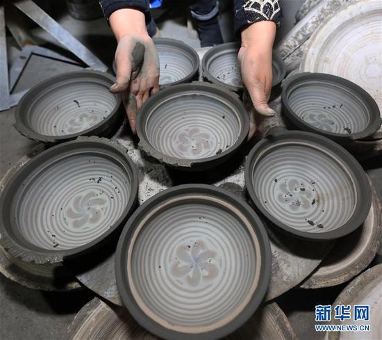10月9日,贵州省毕节市织金县一砂陶制品厂的工人在整理砂陶半成品。新华社发(王纯亮 摄)