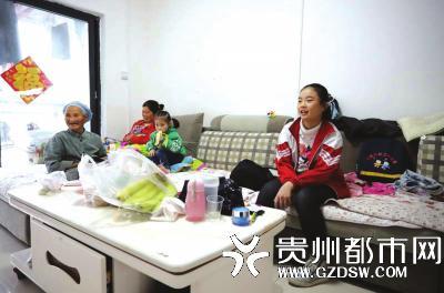 10月16日,在丹寨县金钟易地扶贫搬迁安置点,搬入新家的村民在家里看电视。 黄晓海 摄