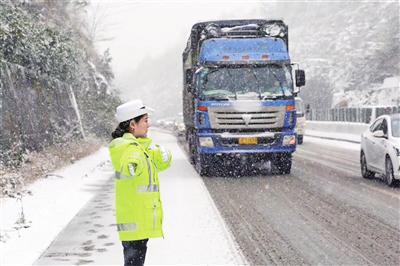 图为在遵赤高速19公里路段,民警王靖正在大雪中指挥车辆有序安全通行。