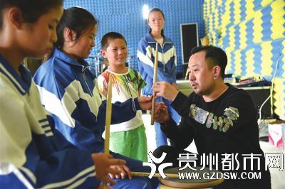 痛仰乐队成员指导孩子们打架子鼓。