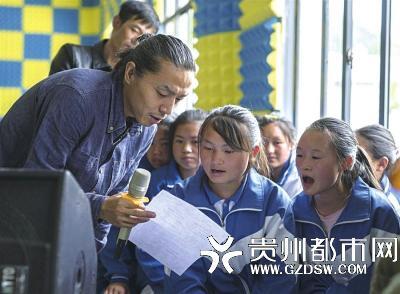 痛仰乐队成员与孩子们一起唱歌。