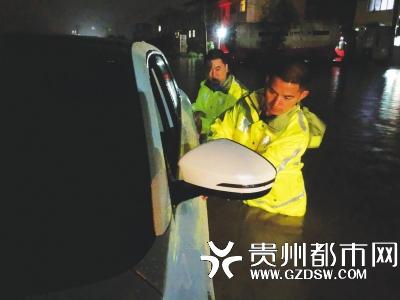 民警蹚水排查积水中车辆是否有被困人员