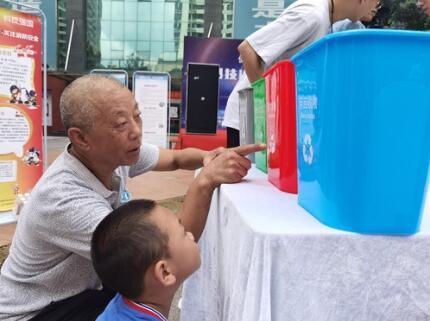 在活动现场,一位家长自发带着小朋友参观学习垃圾分类。记者 李凡 摄