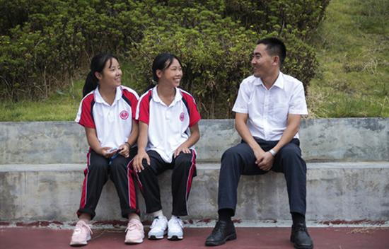 刘秀祥(右)与学生在校园内交谈。