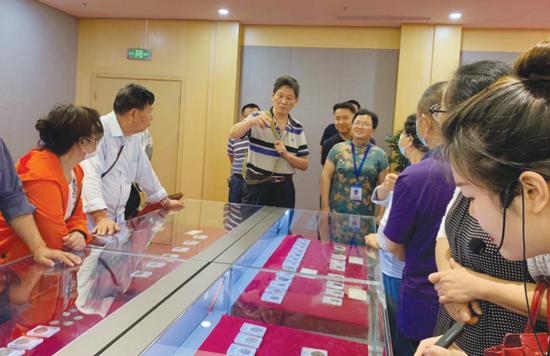 李连昌(中)在展览现场为观展市民讲解古币。