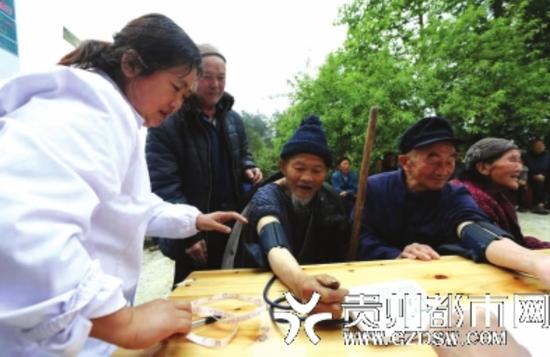 福泉市陆坪镇香坪村,卫生院工作人员为村民测量血压。 肖伟 摄