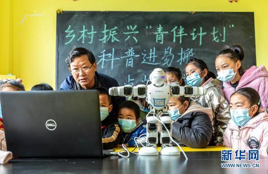"""1月21日,在贵州省毕节市黔西县锦绣街道""""新市民·追梦桥""""服务中心,科普宣传员给易地扶贫搬迁安置点儿童讲解机器人的操作原理。新华社发(范晖摄)"""