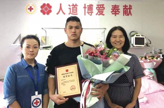 张起榕(中)获捐献造血干细胞荣誉证书。(红十字会供图)