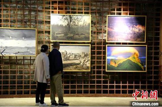 游客在镇远古城观看摄影展。徐伟 摄