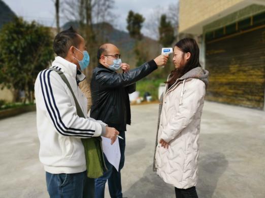 (图为五峰街道班子成员带领网格长对为重点人员测量体温)