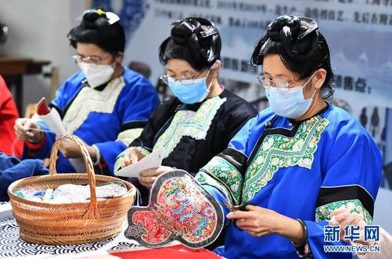 4月2日,在贵州省榕江县卧龙移民小区一刺绣扶贫车间,几名妇女在学习按订单设计的图案刺绣。