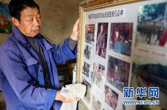 宋光平在擦拭装有父亲宋加通照片的相框。(新华社记者欧东衢2021年4月21日摄)