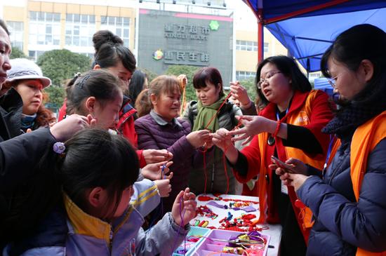 手工制作点的自愿者教市民编织中国结