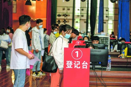 前来接种的贵州中医药大学学生在登记信息。