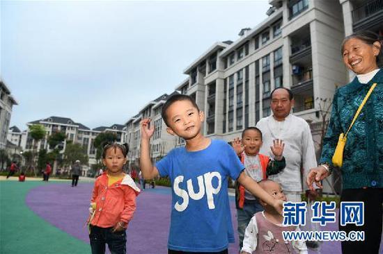在贵州省遵义市正安县瑞濠街道搬迁安置点,搬迁户和孩子们在新居前留影(2019年10月10日摄)。新华社记者 杨文斌 摄